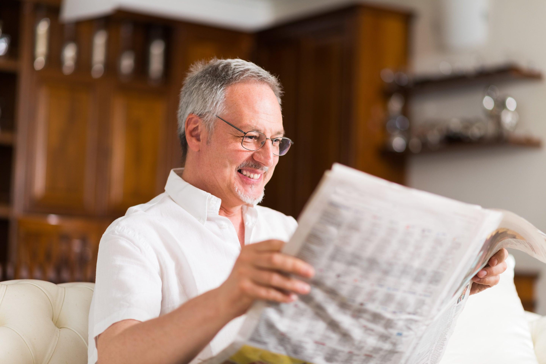 Mature man reading a newspaper | SLENT