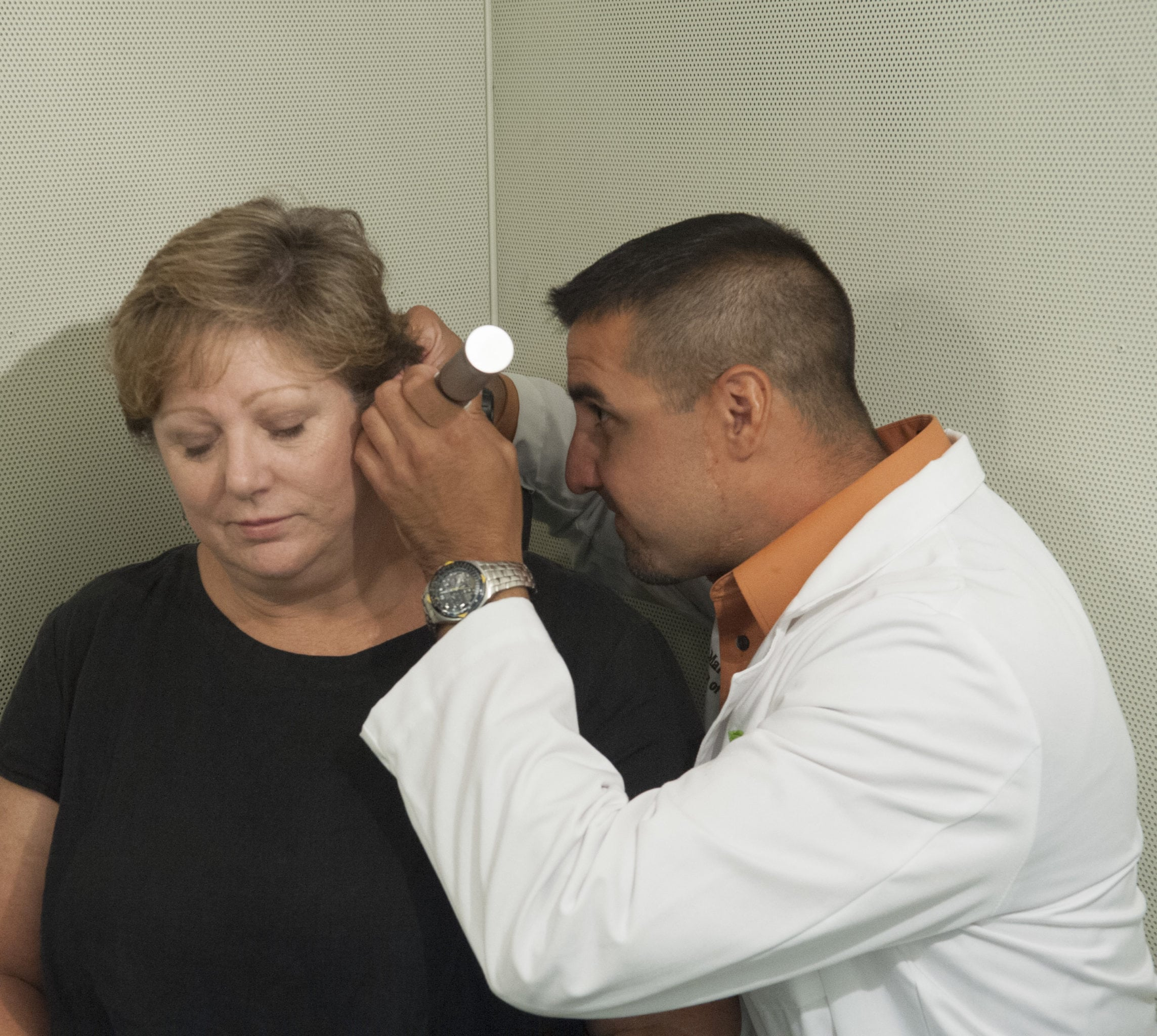 Audiologist looking into ears