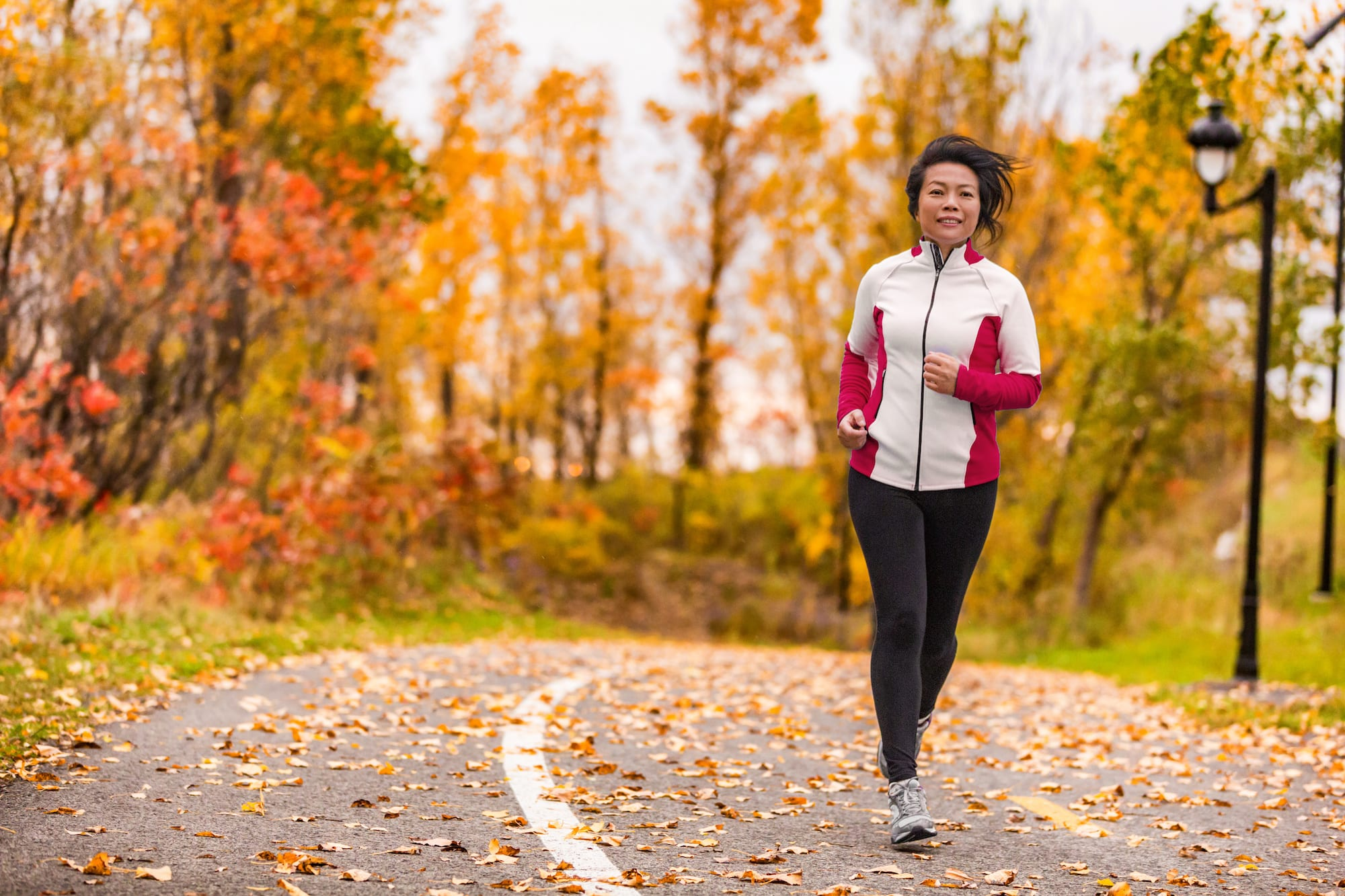 Mature Asian woman running active in her 50s. Middle aged female jogging outdoor living healthy lifestyle in beautiful autumn city park in colorful fall foliage. Asian Chinese adult in her fifties.   SLENT Hearing