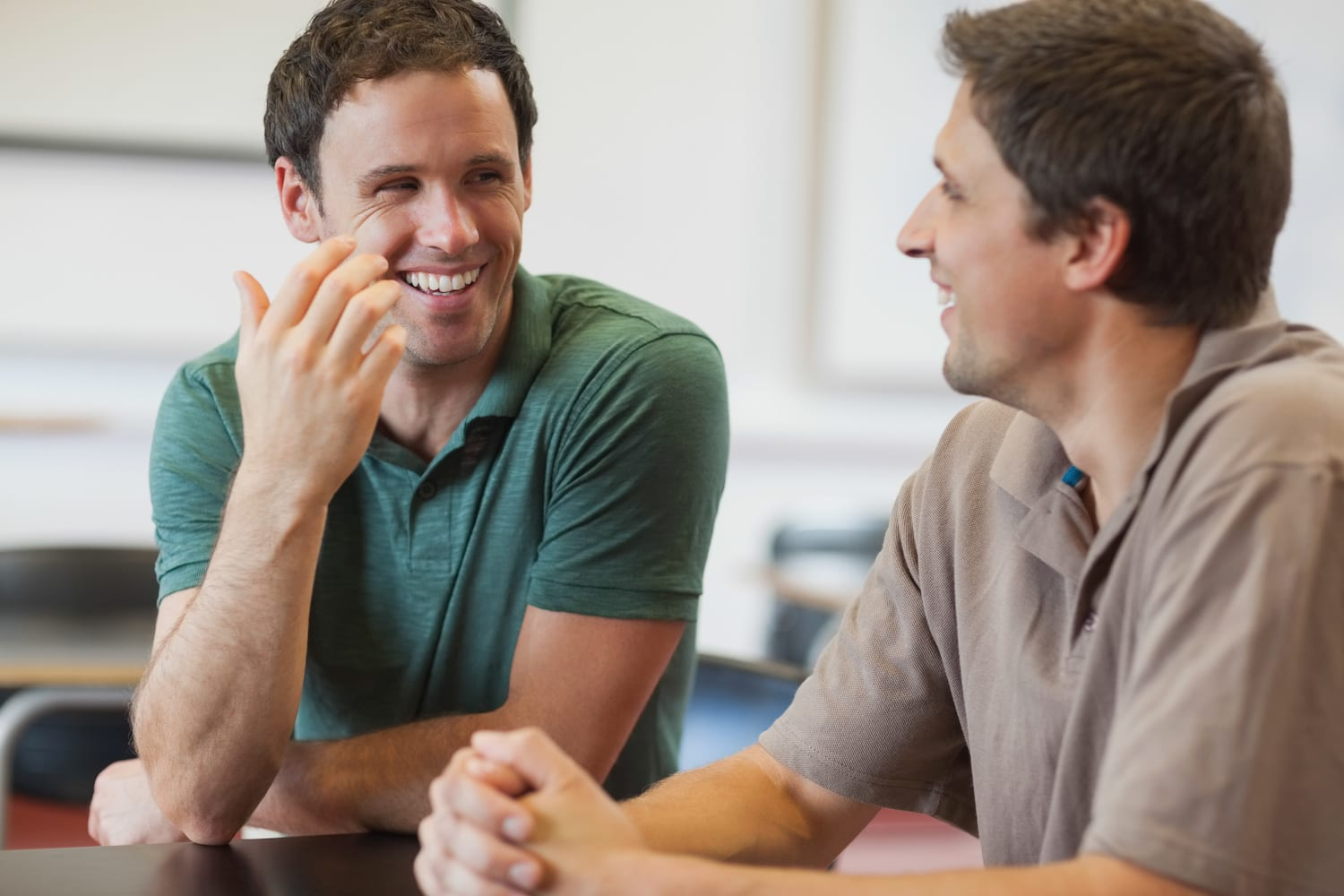 Two friendly male mature students chatting while sitting in class room | SLENT
