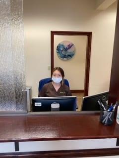 Team member sat at desk wearing face mask